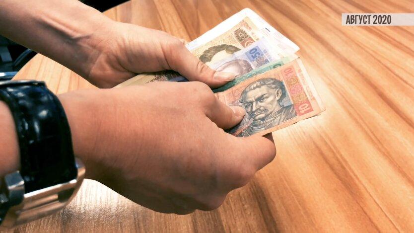 Подсчет гривен в руках: купюры по 100, 50 и 10 гривен