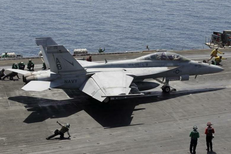 A F/A-18E/F Super Hornets of Strike Fighter Attack Squadron 211 (VFA-211) is lined up for take off on the flight deck of the USS Theodore Roosevelt (CVN-71) aircraft carrier in the Gulf