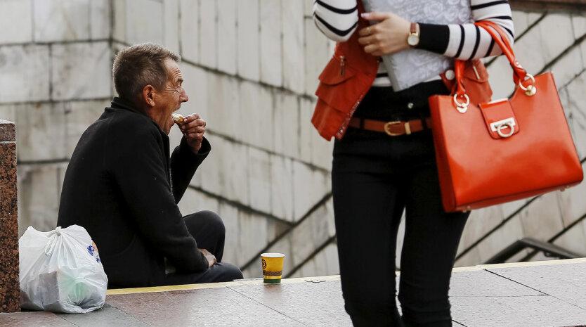 A man eats his sandwich as he begs money near an underground passage in Kiev