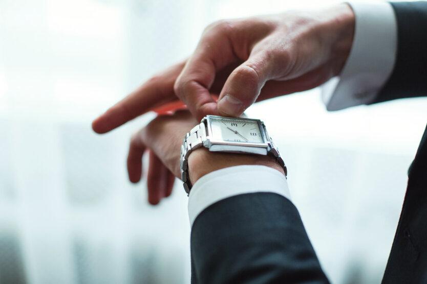 Businessman adjusts clock